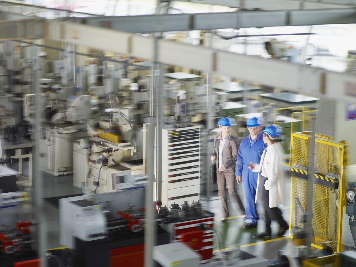 Businesspeople In Hard Hats Walking On Factory Floor